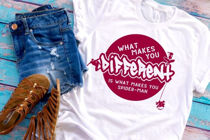 A DIY Spiderman white t-shirt sitting on a blue wood table next to a pair of jean shorts and brown strappy sandals with a raspberry spider-man design that says what makes you different is what makes you spider-man.