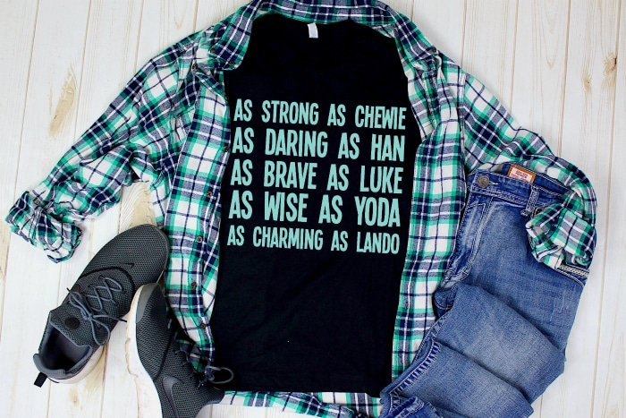 A white, aqua and navy plaid male button down shirt sits over a black tshirt with aqua lettering describing characters from Star Wars, like Strong as Chewie and Wise as Yoda