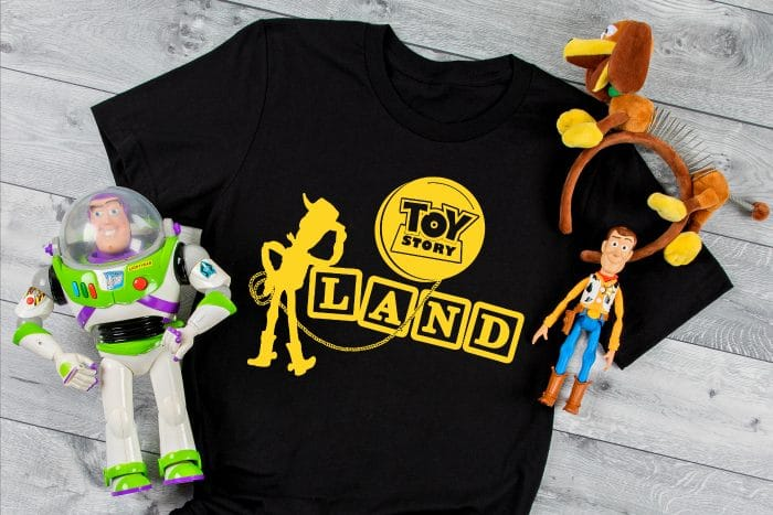 Toy Story Land SVG with Woody is ironed onto black tshirt with heat transfer vinyl as a Disney World Shirt with Slinky Mickey Ears and Woody and Buzz action figures sitting by the shirt.