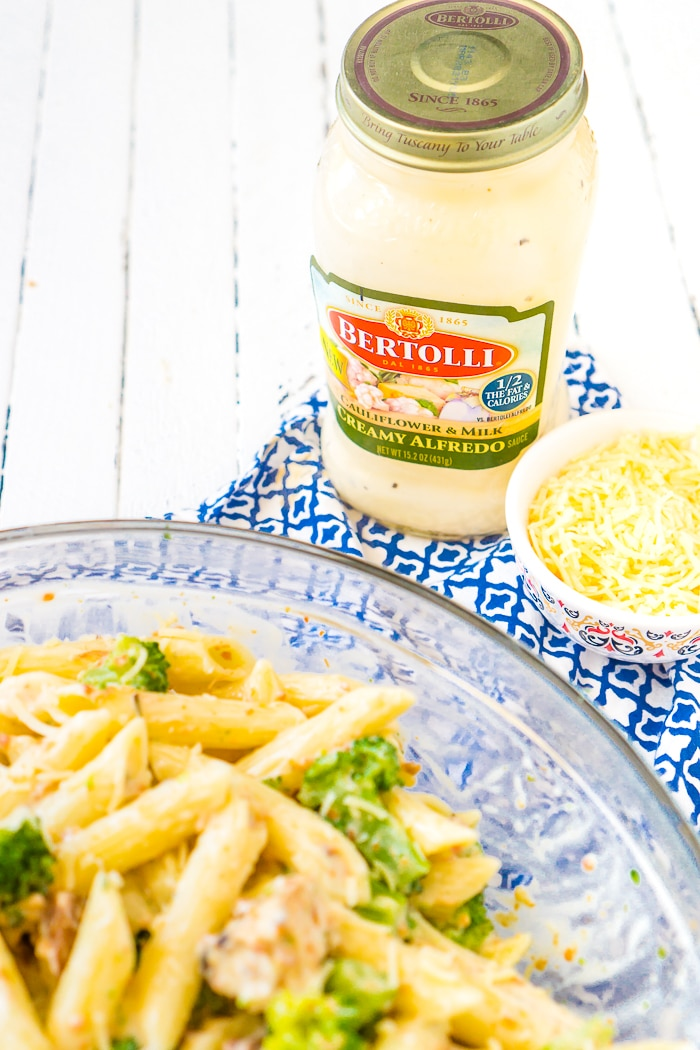 A Jar of Bertolli® Creamy Alfredo with Cauliflower and Milk sauce sits on a blue napkin and a white wood table with a bowl of shredded parmesan cheese to it's right and a clear glass bowl of broccoli bacon chicken alfredo pasta out of focus in front.