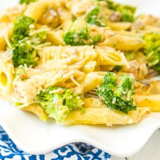 Up close photo of a wavy white plate sitting on a blue and white napkin topped with a serving of penne pasta with chicken, bacon, and broccoli that is coated with a lighter Alfredo sauce made with cauliflower.