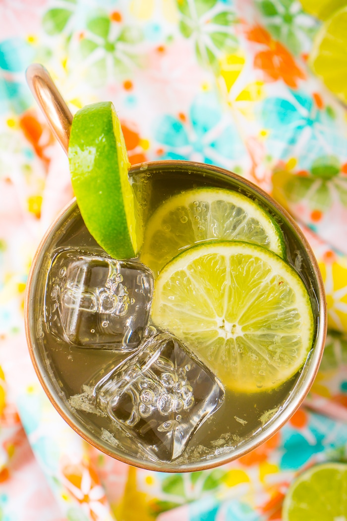 A top down photo of a coral, green and blue floral napkin with a copper mug of moscow mule resting on top. The moscow mule is topped with fresh limes and filled full of ice to keep the summer cocktail cold.