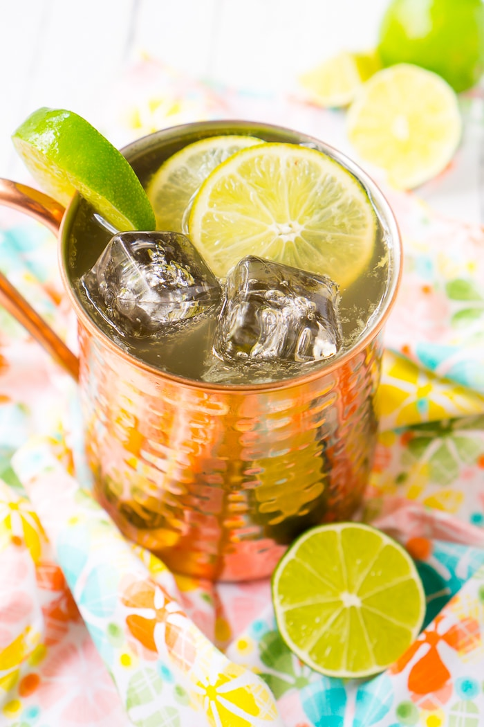 A copper mug filled with square ice cubes, slices of limes, and a classic moscow mule recipe sits on top of a coral and blue floral napkin on top of a white wood table with extra limes sitting on the table.