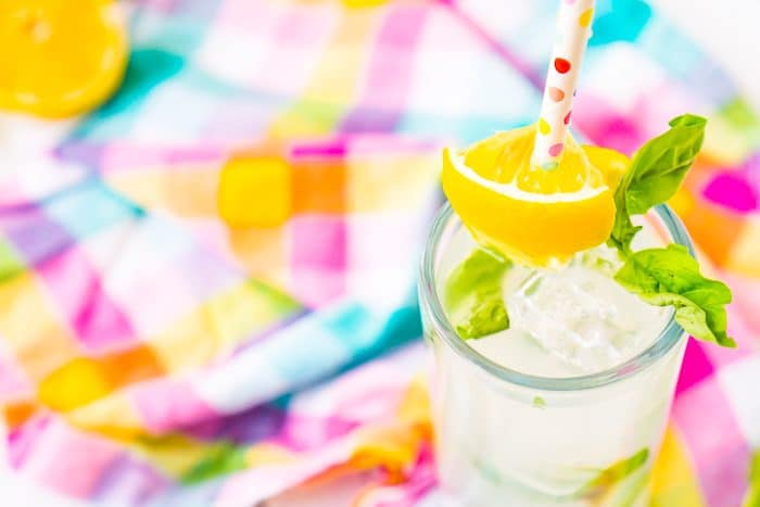 Tall thin glass sits in the bottom right corner the photo and is filled with square ice cubes, fresh basil leaves, and vodka lemonade with a white straw with colorful polka dots and a lemon wedge as a garnish.