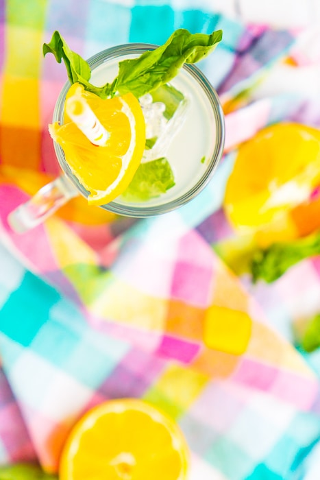 Straight down shot onto a white wood plank table and a brightly colored plaid napkin in pinks, purples, yellows and aqua with lemon wedges sitting out of focus and a skinny round glass filled with basil lemonade and topped with a polkadot paper straw, basil leaves, and a lemon wedge.