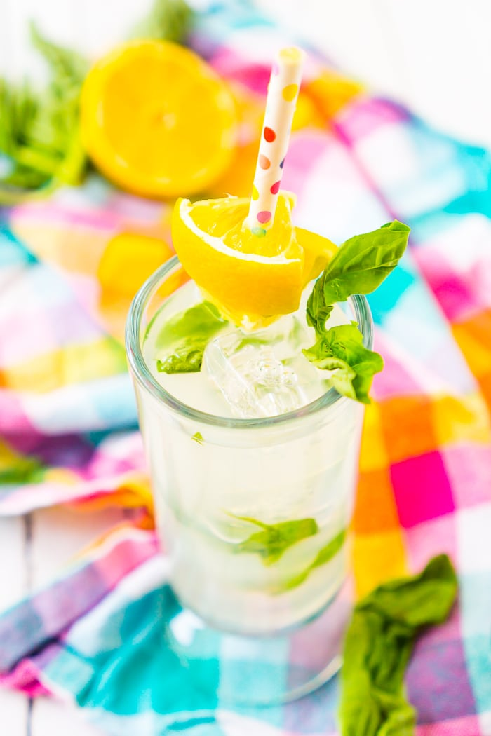 Tall skinny highball glass is filled with basil lemonade, vodka, and square ice cubes with a lemon wedge garnish that is on a colorful polkadot paper straw. A bright plaid napkin sits on the table behind it as well as half a lemon and basil leaves out of focus.