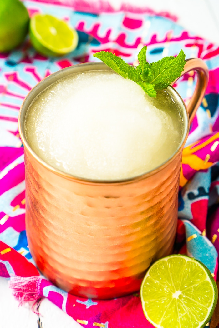 Tall copper mug is filled with frozen mocow mule slushie and garnished with a sprig of mint and resting on a bright pink and blue napkin with extra limes in the top left corner out of focus.