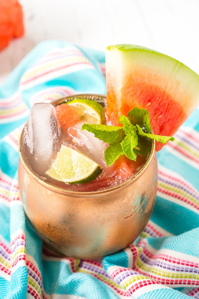 Copper mug rests on a bright blue napkin with colorful stripes with a fresh watermelon wedge standing upright on the rim with a sprig of mint in front of it and watermelon Moscow mule inside.