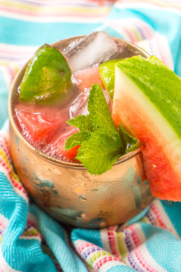 Fresh watermelon moscow mule in a copper mug is topped with fresh cubes of watermelon, lime wedges, a sprig of mint, and a triangle watermelon wedge resting on the rim of the glass.