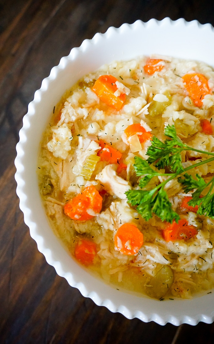 Straight down shot of a white soup bowl with zipzag edge filled with lemon chicken orzo soup with chunks of carrots, chicken, and celery and a parsley sprig garnish.