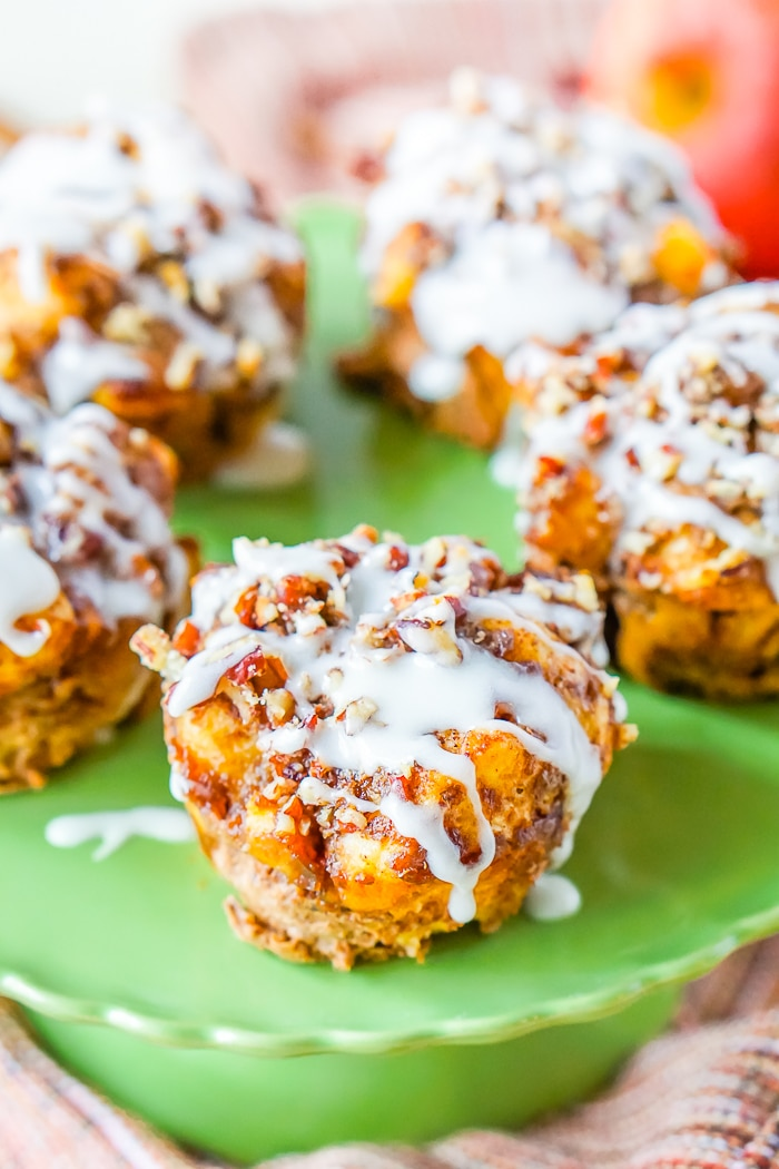 An up close photo of muffins topped with chopped pecans and drizzled in a white icing that sit on a green ruffled cake plate.