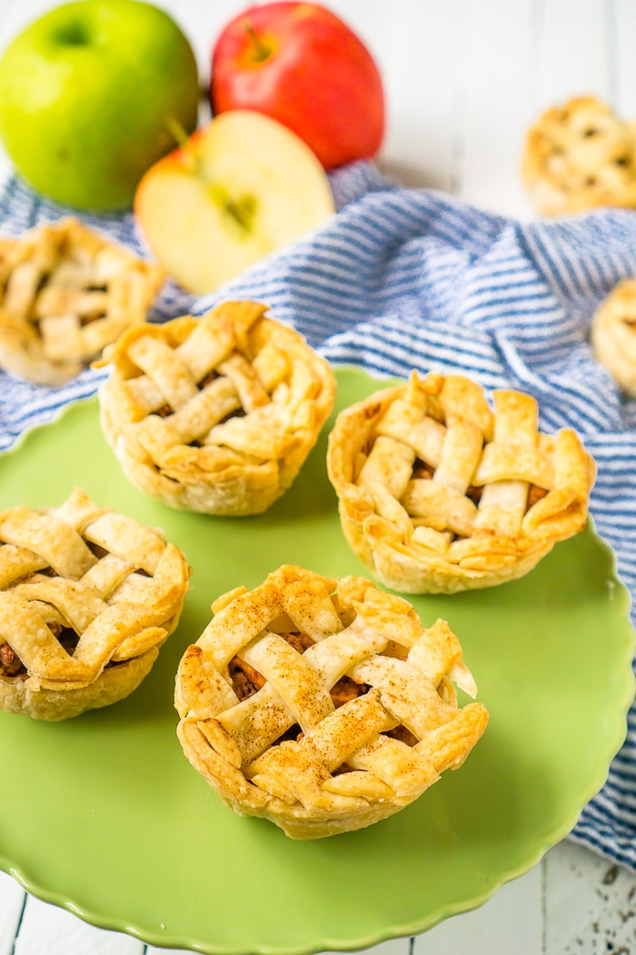 GREEN CAKE PLATE WITH 4 MINI APPLE PIES SITS ON TOP OF A BLUE STRIP NAPKIN ON A WHITE WOOD PLANK TABLE WITH BOTH RED AND GREEN APPLES IN THE TOP LEFT CORNER