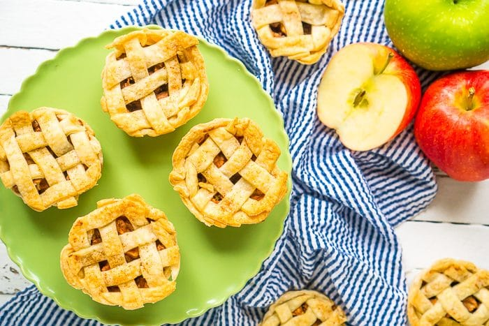 STRAIGHT DOWN SHOT OF A GREEN CAKE PLATE WITH 4 MINI APPLE PIES ON IT WITH A NAVY BLUE STRIPED NAPKIN ON THE TABLE IN THE BACKGROUND WITH A RED AND GREEN APPLE AS WELL AS OTHER PIES.