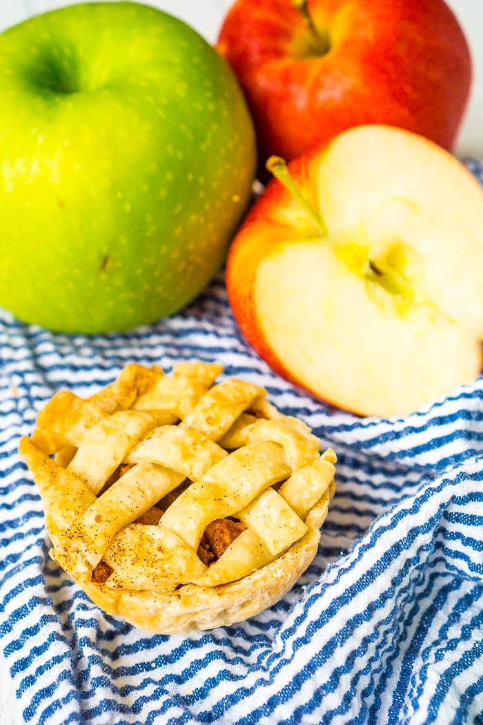 A BLUE STRIPED NAPKIN HAS A SMALL INDIVIDUAL APPLE PIE RESTING ON TOP WITH A GREEN AND RED APPLE IN THE BACKGROUND