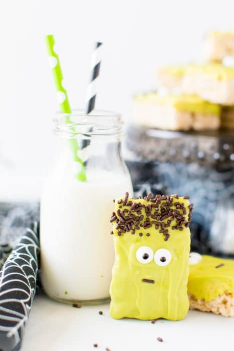 A frankenstein rice krispie treat coated in vibrant green candy melt and given candy eyes and brown sprinkle hair is propped up on a small milk jug with a green paper straw and a black paper straw