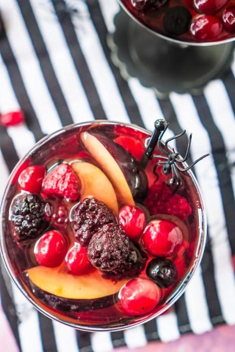 Round champange coupe glass sits on a white and black stripe tablecloth and is filled with a dark red sangria and fresh berries and garnished with a black spider for a Halloween Sangria