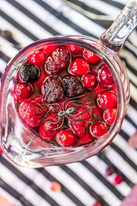 A tall curved glass pitcher is filled with a pink sangria and topped with blackberries, blueberries, cranberries and raspberries. A fake plastic spider sits on top of the fruit.