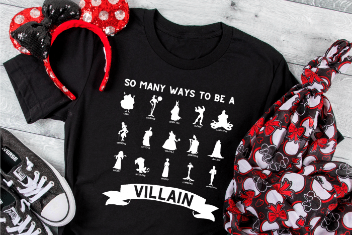Black tshirt with a white iron on heat transfer vinyl design that says So Many Ways to be a Villain with popular Disney Villain silhouettes sits on a gray wood table with sequined minnie ears and a minnie scarf resting near by.