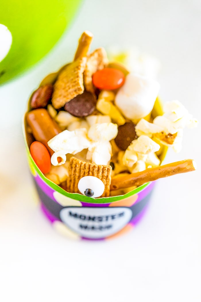 A top down shot onto a small party cup with the words monster mash on the outside and a halloween trail mix on the inside with candy eyes, reese's pieces, marshmallows and more inside!