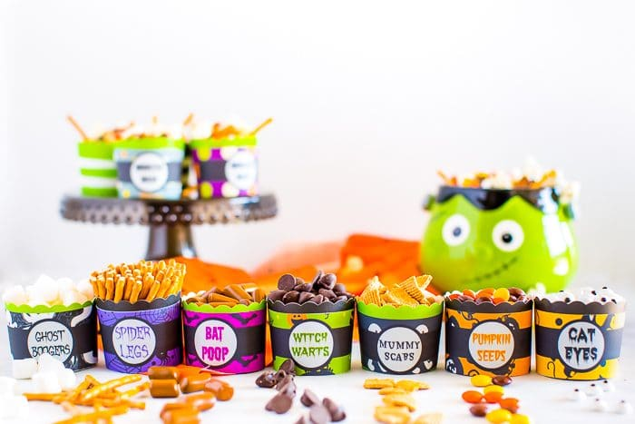 Small round paper cups with phrases like witch warts and mummy scabs are lined up in a row with a Frankenstein snack bowl full of mixed ingredients for Halloween Monster Mash is in the background.