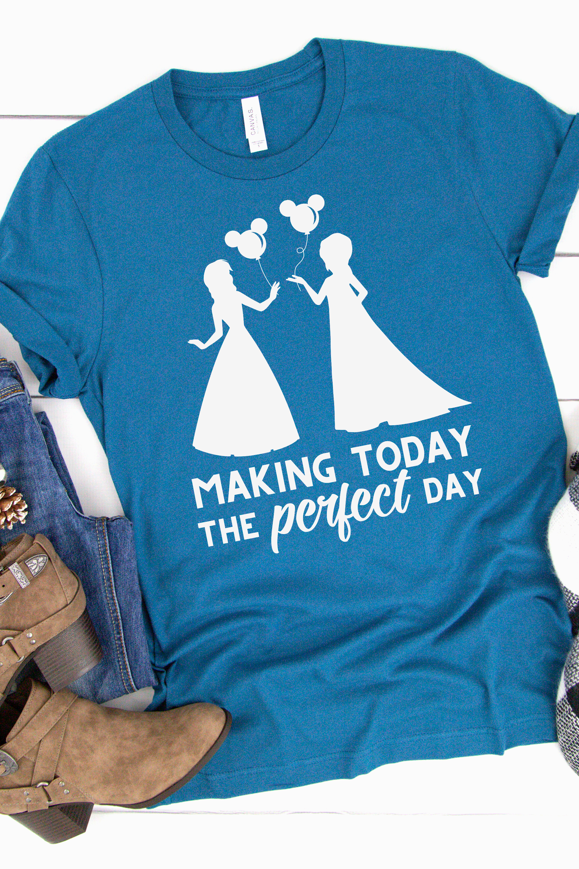 Blue shirt with a Frozen svg file ironed on using heat transfer vinyl in white that say making today the perfect day and features an anna and elsa silhouette holding mickey balloons